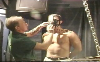 muscle hunk is prepped in leather straitjacket