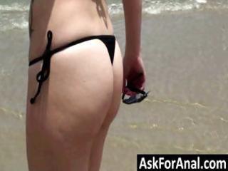 Cute brunette in a bikini is on the beach walking